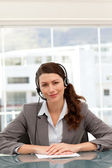 Cute businesswoman on the phone with earpiece sitting at a table — Stock Photo