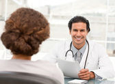 Cheerful hispanic doctor dring an appointment with a patient — Stock Photo