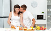 Affectionate man kissing his girlfriend while cutting bread for — Stock Photo