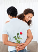Mooie vrouw vinden een roos verborgen door zijn vriend — Stockfoto