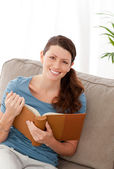 Happy woman holding a book sitting on her sofa — Stock Photo