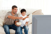 Happy father and son watching television while eating pop corn — Stock Photo