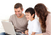 Cute family working on their laptop together sitting on the sofa — Stock Photo