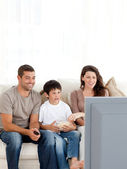 Happy family watching television while eating popcorn together — Stock Photo