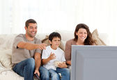 Family laughing while watching television together — Stock Photo