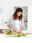 Pretty woman cutting vegetables while preparing a salad — Stock Photo