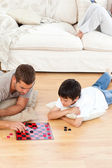 Father and son playing checkers together lying on the floor — Stock Photo