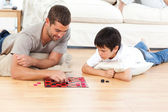 Handsome man playing checkers with his son lying on the floor — Stockfoto