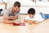 Homem bonito, jogando damas com o seu filho deitado no chão — Foto Stock