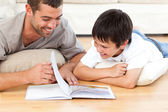 Cute boy reading a book with his father on the floor — Stock Photo