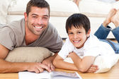 Portrait of a father and son reading a book together on the floo — Stock Photo