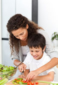 Attentive mother helping her son to cut vegetables — Stock Photo