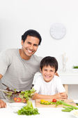 Portrait of a father and his son preparing their lunch — Stock Photo