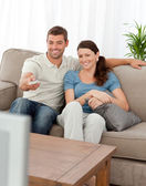 Happy man changing channel while watching television with his wi — Stock Photo