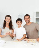 Cute boy with his parents in his kitchen — Stock Photo
