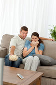 Terrified couple watching a horror movie in the living room — Stock Photo