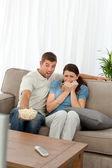 Aterrada pareja viendo una película de terror en la sala de estar — Foto de Stock