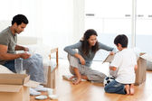Happy family packing dishes together in their living-room — Stock Photo