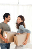 Lovely couple holding cardboards in their living-room — Stock Photo