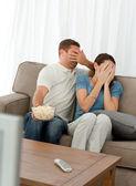Encantadora pareja ocultando su cara de una película de terror en t — Foto de Stock