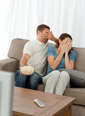 Lovely couple hiding their face from a horror movie sitting in t — Foto de Stock