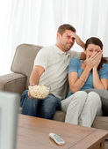 Terrified couple watching a horror movie — Stock Photo