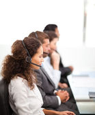 Four representatives on the phones with earpiece on — Stock Photo