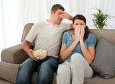 Scared couple eating pop corn while watching a horror movie — Foto de Stock