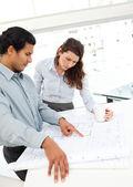Arquitetos sérios olhando para planos de pé em uma mesa — Foto Stock