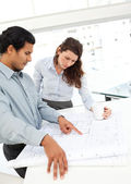 Serious architects looking at plans standing at a table — Foto Stock