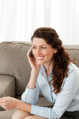Cheerful businesswoman on the phone sitting on the sofa — Stock Photo