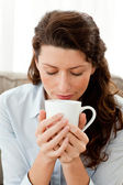 Pretty businesswoman smelling her coffee sitting on the sofa — Stock Photo