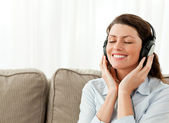 Happy businesswoman relaxing with music in the living-room — Stock Photo