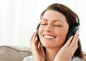 Pretty businesswoman relaxing with music sitting on the sofa — Stock Photo
