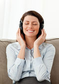Smiling woman listening music with heaphones in the living room — Stock Photo