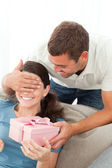 Happy woman receiving a gift from her boyfriend in the living ro — Stock Photo