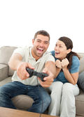 Cheerful woman encouraging her boyfriend playing video game — Stock Photo