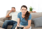 Serious woman playing video game while her boyfriend waiting for — Zdjęcie stockowe