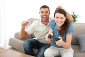Cheerful man encouraging his girlfriend playing video game — Stock Photo