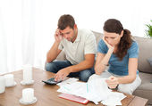 Desperate couple doing their accounts sitting on the sofa — Stock Photo