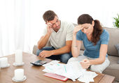 Worried couple doing their accounts in the living room — Stok fotoğraf