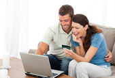 Happy couple looking at their accounts online sitting on the sof — Stock Photo