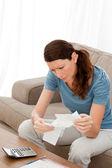 Kobiety obawiają się, patrząc na jej rachunki siedzi na jej kanapie — Zdjęcie stockowe