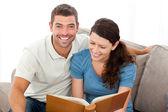 ženské čtení knihy se svým přítelem na pohovce — Stock fotografie