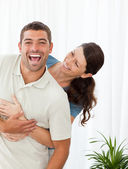 Joyful couple laughing topgether in the living-room — Stock Photo