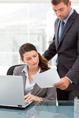 Handsome manager showing a paper to a businesswoman while workin — Stock Photo