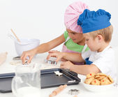 Cute sibling baking cookies together in the kitchen — Stock Photo