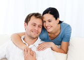 Lovely woman hugging her boyfriend while relaxing on the sofa — Stockfoto