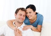 Mooie vrouw haar vriendje knuffelen terwijl u ontspant op de bank — Stockfoto