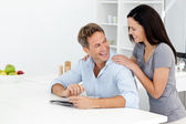 Happy couple doing a cryptic crossword together — Stockfoto